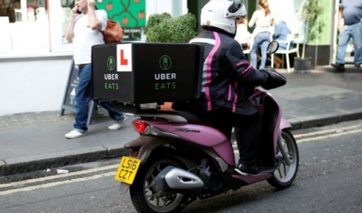 An UberEATS food delivery courier rides her scooter in London